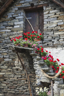 Switzerland, Ticino, Sonogno, typical historic stone houses with summer flowers on staircase - GWF05972