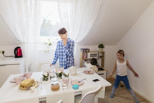Duisburg, NRW, Deutschland. Eine lesbische Frau mit zwei Kindern bereiten Frühstück in der Küche  vor - KMKF00771