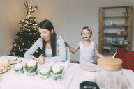 Woman with little son in the kitchen at Christmas time - KMKF00777