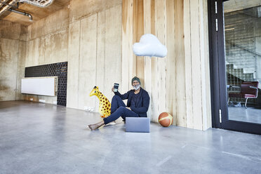 Relaxed businessman sitting on floor with coffee, laptop, ball and giraffe figurine - FMKF05424