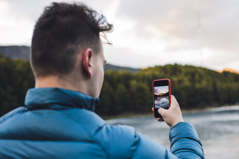 Young man taking cell phone picture at a frozen lake in winter - ACPF00479