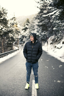 Young man standing on a snowy road with trees in the background - ACPF00482