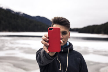 Young man holding red cell phone at a lake in winter - ACPF00485