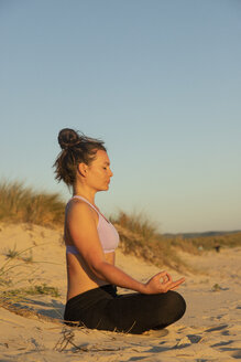 Woman meditating on the beach in the evening - KBF00539