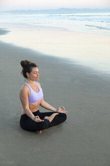 Woman meditating on the beach in the evening - KBF00545