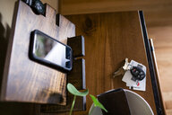 High angle view of car keys with credit cards and smart phone on wooden table at home - CAVF62333