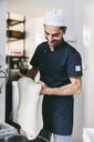 Smiling chef kneading dough using machine in commercial kitchen at pizzeria - CAVF62339