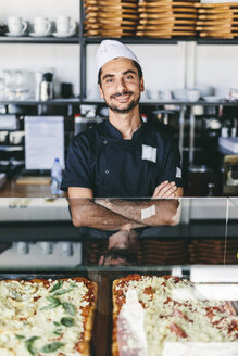 Portrait of confident smiling chef with arms crossed standing in pizzeria - CAVF62351