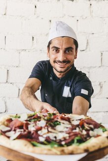 Portrait of smiling chef with cooked pizza on cutting board in pizzeria - CAVF62354