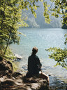Rear view of woman looking at lake while sitting on rocks in forest during sunny day - CAVF62363