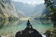 Female tourist looking at lake while sitting on rock against mountains - CAVF62375