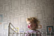 Low angle view of cute girl with pacifier in mouth looking away while standing against wall at home - CAVF62423