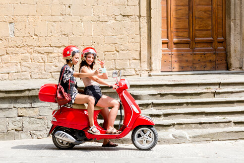 Friends taking selfie on scooter by church entrance, Città della Pieve, Umbria, Italy - CUF49472