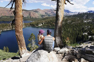Rear view of couple looking at lake while sitting on rocks during sunny day - CAVF62439
