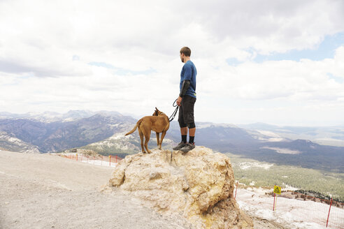 Side view of man with dog looking at landscape while standing on rock against cloudy sky - CAVF62448