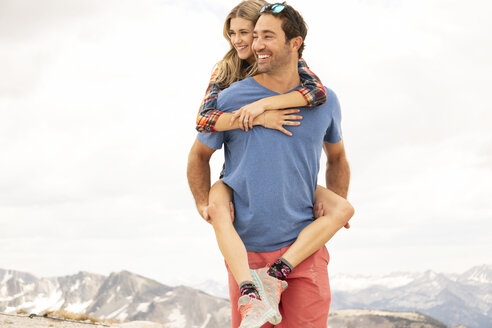 Happy boyfriend piggybacking girlfriend while standing on mountain against cloudy sky - CAVF62451