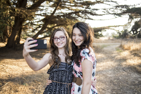 Happy sisters talking selfie with smart phone while standing against trees in forest - CAVF62475