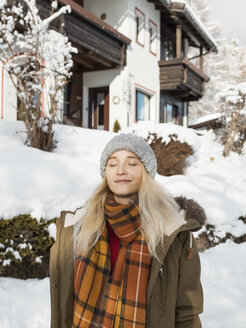 Smiling young woman with eyes closed wearing warm clothing in town during winter - CAVF62511