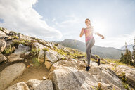 Confident female hiker running on rocks against sky during sunny day - CAVF62520