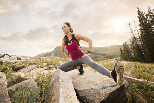 Low angle view of confident female hiker exercising on rocks against cloudy sky in forest - CAVF62523