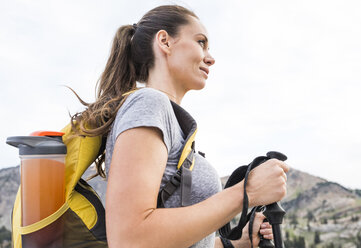 Low angle view of smiling female hiker looking away while standing against sky in forest - CAVF62526