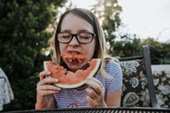 Girl wearing eyeglasses eating watermelon while sitting on chair against trees in yard - CAVF62604