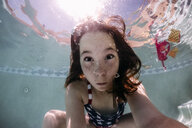 Portrait of girl making face while swimming in pool during sunny day - CAVF62607