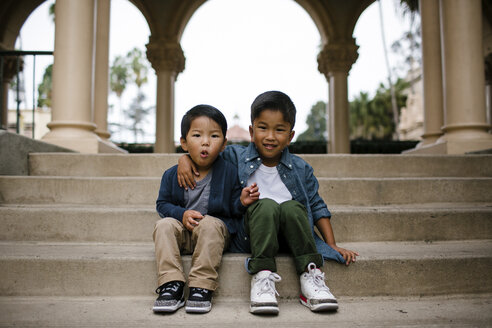 Portrait of cute brothers sitting on steps against sky in Balboa Park - CAVF62643