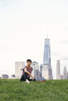 Thoughtful woman looking away while sitting on grassy field against cloudy sky in city - CAVF62658