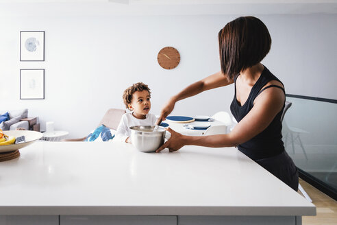 Son looking at mother preparing food on kitchen island while standing against wall - CAVF62667