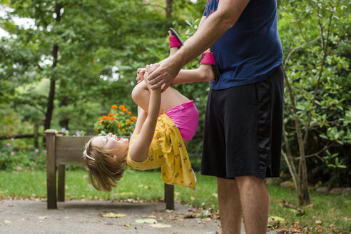 Midsection of playful father carrying cute daughter while standing against trees in yard - CAVF62691