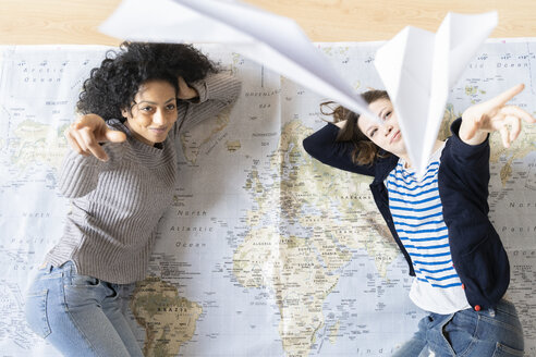 Friends lying on map, throwing paper palnes, planning their vacations - FMOF00419