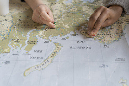 Friends putting pins on a map, planning their vacations, close up - FMOF00422