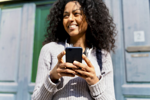 Laughing woman holding smartphone - FMOF00440