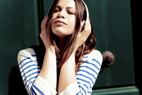 Young woman listening music with eyes closed - FMOF00443