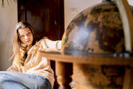 Young woman sitting by globe, looking for travel destinations - FMOF00452