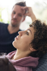 Man watching his wife relaxing on the couch - JOSF03095