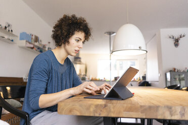 Young woman sitting at table, using digital tablet - JOSF03098
