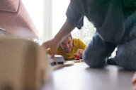 Father and son playing at home with a toy train - JOSF03101