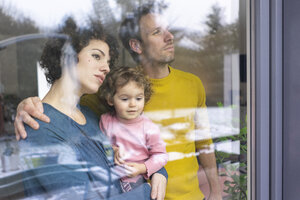 Happy family looking out of window, mother carrying daughter - JOSF03104