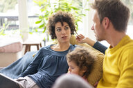 Family lying on couch watching movie on theit tablet - JOSF03110