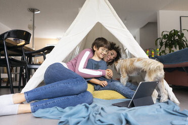 Mother and son lying in play tent with dog - JOSF03122