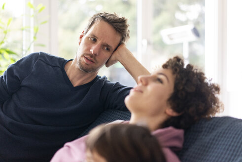 Man watching his wife relaxing on the couch - JOSF03128