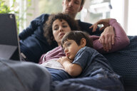 Family lying on couch watching movie on theit tablet - JOSF03134