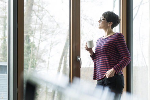 Woman with coffee mug looking out of terrace door - SBOF01824