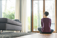 Back view of woman sitting on the floor of living room looking out of window - SBOF01827