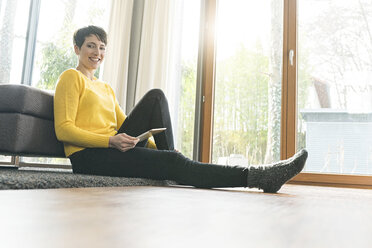 Portrait of happy woman with digital tablet sitting on the floor of living room - SBOF01833