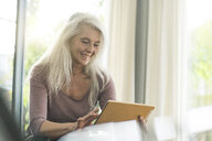 Portrait of happy mature woman using  digital tablet at home - SBOF01836