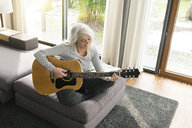 Mature woman sitting on couch at home playing guitar - SBOF01839