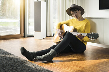 Woman sitting on the floor of living room playing guitar - SBOF01842